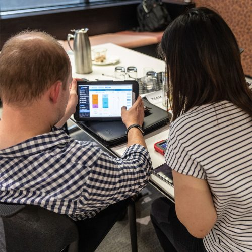 Man and lady look at tablet screen with simulation game
